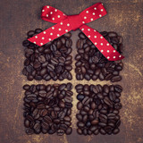 Fototapety A red ribbon bow on top of a dark roasted coffee beans present o