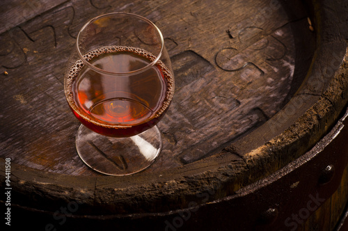 Glasses of brandy in cellar with old barrels Poster