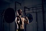 Fototapety Closeup of man lifting barbells at gym
