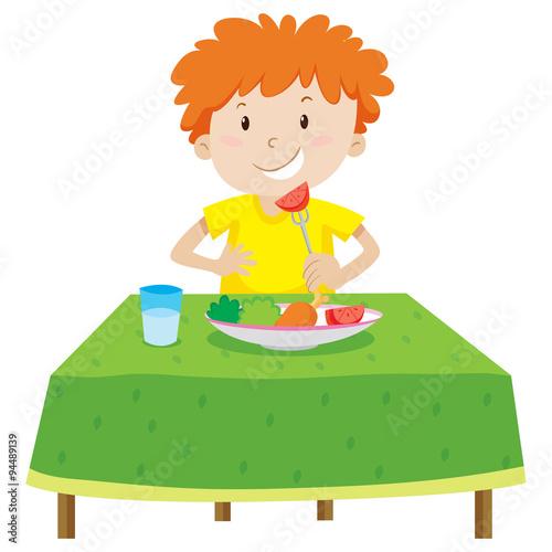 Fototapeta Little boy eating on the table
