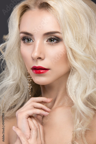 Beautiful blond woman with evening make-up, red lips and curls Poster