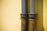 Detail of pair of downpipes copper and cast iron on a colorful facade poster