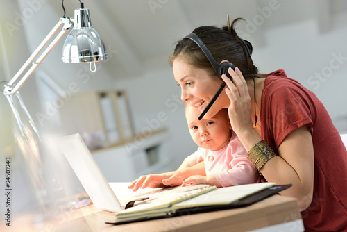 Busy businesswoman working with baby on lap Poster