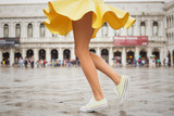 Cheerful young woman wearing sneakers and yellow skirt