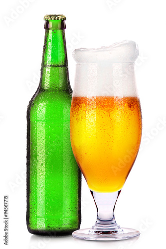 Glass and bottle of beer with drops isolated on white
