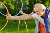 Fototapety Senioren machen Sport mit Reifen im Garten