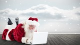 Fototapety Composite image of santa lies in front of his laptop