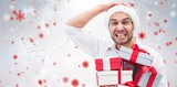 Fototapety Composite image of festive man holding christmas gifts
