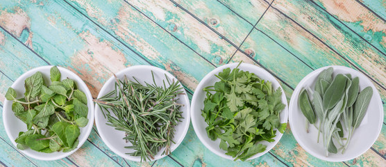 Basil leaves, rosemary. mint, parsley and sage leaves herbs in white bowl over wooden background © akulamatiau