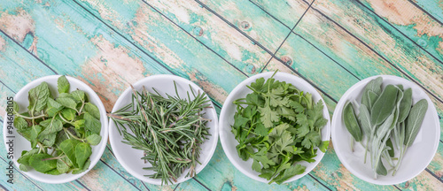 Basil leaves, rosemary. mint, parsley and sage leaves herbs in white bowl over wooden background