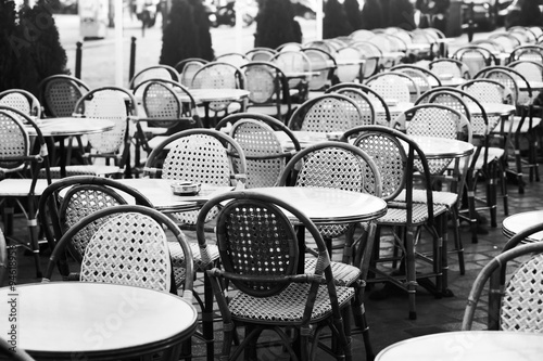vintage street cafe in Paris, black and white photo of wicker chairs and tables - 94618956