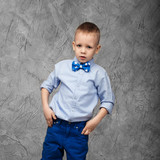 Portrait of a cute little boy in jeans, blue shirt and bow tie o