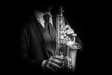Fototapety Detail of Saxophone and man hands isolated against black backgro