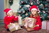 Веселые дети в костюмах Санта Клауса с подарками под новогодней ёлкой