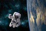 Fototapety An astronaut floats in the zero gravity environment of space - Elements of this image furnished by NASA.