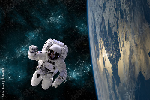An astronaut floats in the zero gravity environment of space - Elements of this image furnished by NASA. - 94801589