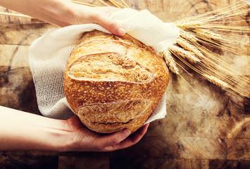 Baker holding a loaf of bread on rustic bacgkround