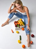 woman eating near box with fresh organic vegetables and fruits