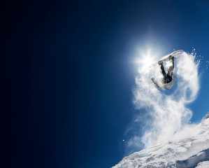 Snowboarder making high jump in clear blue sky. Concept: fun, sport, courage, adventure, danger, extreme. Large copy space on the left side. © rcaucino