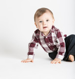 a cute 1 year old baby stands in white studio with jeans and a red white flannel looking camera left in excitement