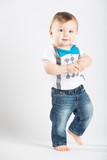a cute 1 year old is walking in a white studio setting. The boy has a cute expression. He is dressed in Tshirt, jeans, suspenders and blue bow tie