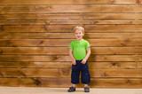 little boy in green shirt near wooden wall