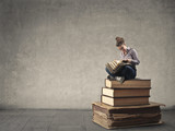 Young woman reading while sitting on a pile of books