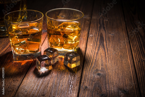 Two glasses of whiskey with ice on wooden table Poster