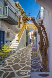 Streetview of Mykonos town with yellow chairs and tables and stairs, Greece