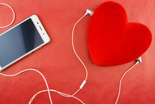 Heart with smartphone and earphones closeup on red