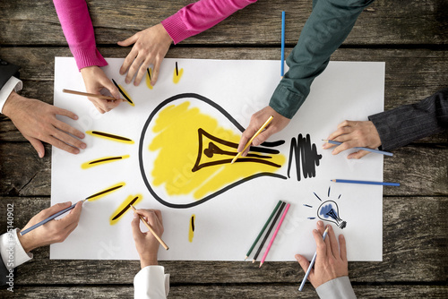 Six people, men and women, drawing bright yellow light bulb on a Poster