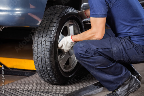 Fotografiet Mechanic Fixing Car Tire At Repair Shop