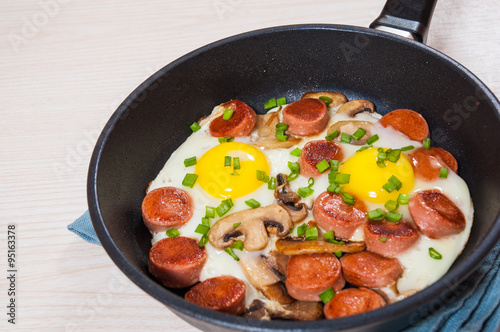 Фото: fried eggs with mushrooms and sausage in a frying pan