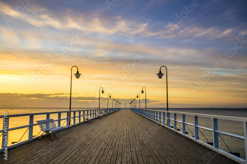 Fototapety, obrazy : wooden pier by the sea lit by stylish lamps at night