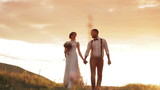bride and groom holding hands walking in the sunset