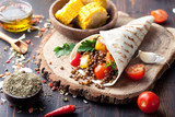Fototapety Vegan tortilla wrap, roll with grilled vegetabes, lentil, corn cob.