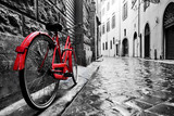 Fototapety Retro vintage red bike on cobblestone street in the old town. Color in black and white