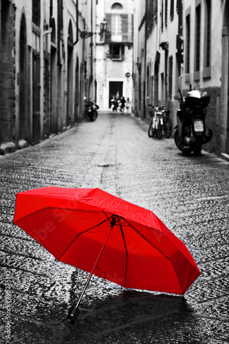 Obraz na płótnie Red umbrella on cobblestone street in the old town. Wind and rain