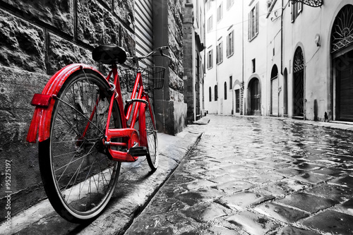 obraz PCV Retro vintage red bike on cobblestone street in the old town. Color in black and white