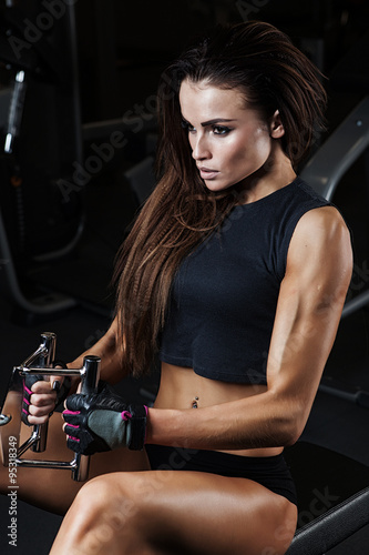 Fototapeta Sexy fitness brunette doing triceps exercises in the sport gym