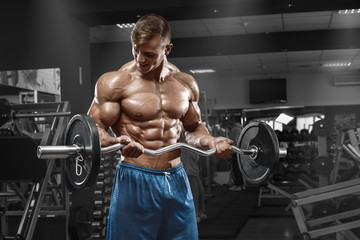 Muscular man working out in gym doing exercises with barbell at biceps, strong male naked torso abs