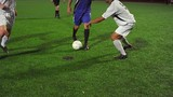 A soccer player dribbles down the field during a game at night