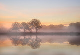 Fototapety Stunning vibrant Autumn foggy sunrise English countryside landsc