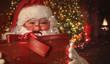 Obrazy na płótnie, fototapety, zdjęcia, fotoobrazy drukowane : Closeup of Santa holding gift with Christmas scene in background