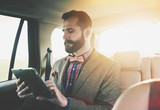Fototapety businessman sitting on back seat of car and touching tablet