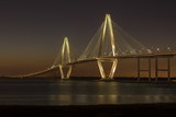 Fototapety Arthur Ravenel Jr. Bridge illuminated aginst a darkening dusk sky.  The bridge carries eight lanes of traffic over the Cooper River between Charleston and Mount Pleasant, SC.