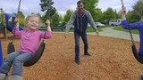 Cute little girls smile big while being pushed by their dad on a swing