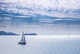 Fototapety Sailing boat on blue sea waters with clear blue sky