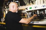 Hombre prepara suculento cafe en un bar. Gente real.