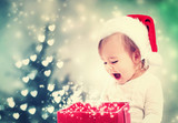 Happy Toddler girl looking at Christmas present box - Fine Art prints